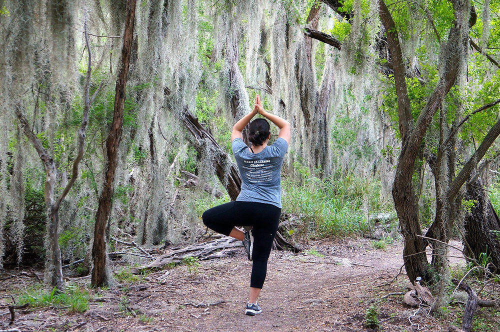 woman does yoga pose on nature trail