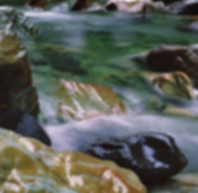 Glacier-blue water over rocks in the North Fork. Photo: Brett Baunton