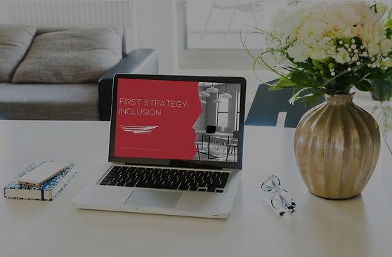 Laptop, notebook and floral arrangement on desk