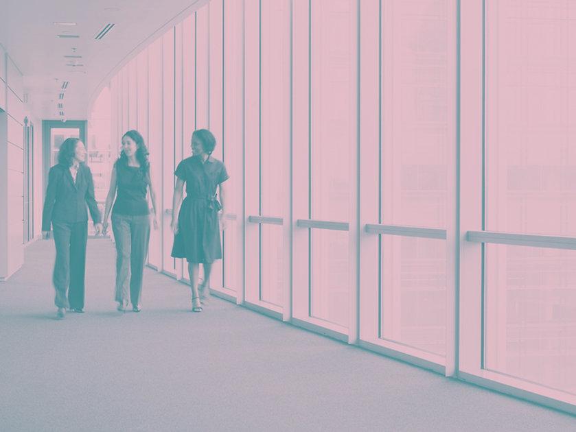 Three women walking down a hallway