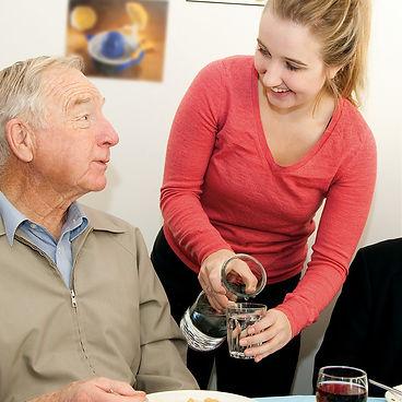 volunteer helping older man meals on wheels