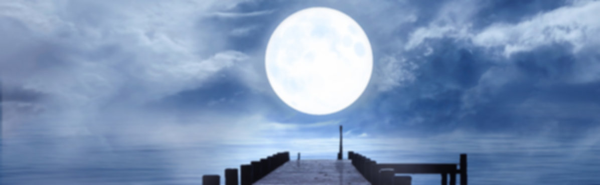 moonlight over a blue sky and blue water with a jetty