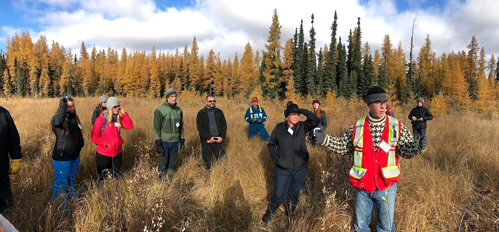 Michael Cody from Cenovus Energy (right, in the vest) describes the outcomes of treatment trials conduction on a restored oil-sands exploration (OSE) well site located in a treed wetland.