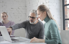 mature-man-using-laptop-while-discussing