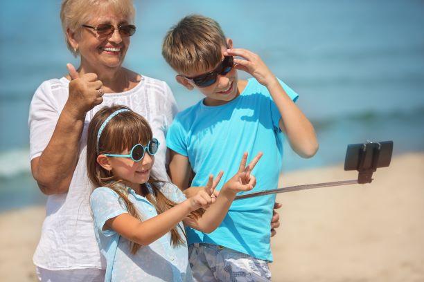 Grandma and grandchildren taking selfie on beach