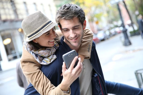 Couple looking at the 8 must have luxury travel apps on phone