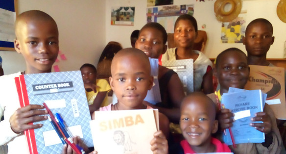 Kids Receiving Exercise Books from our rental office