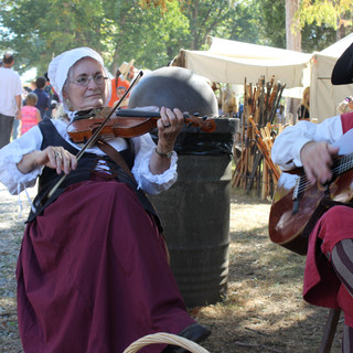 Strolling musicians entertain the crowds.