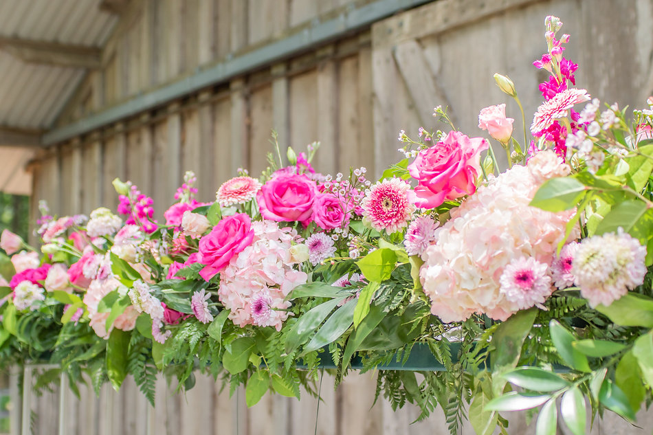 Bright pink wedding flowers in front of barn
