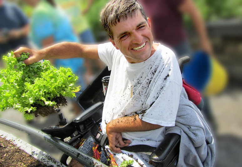 Smiling disabled man in a wheelchair gardening