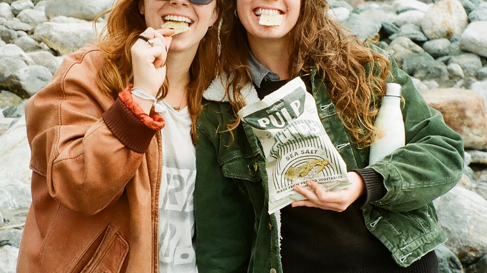 2 girls eating Pulp Chips, now a Plastic Neutral product