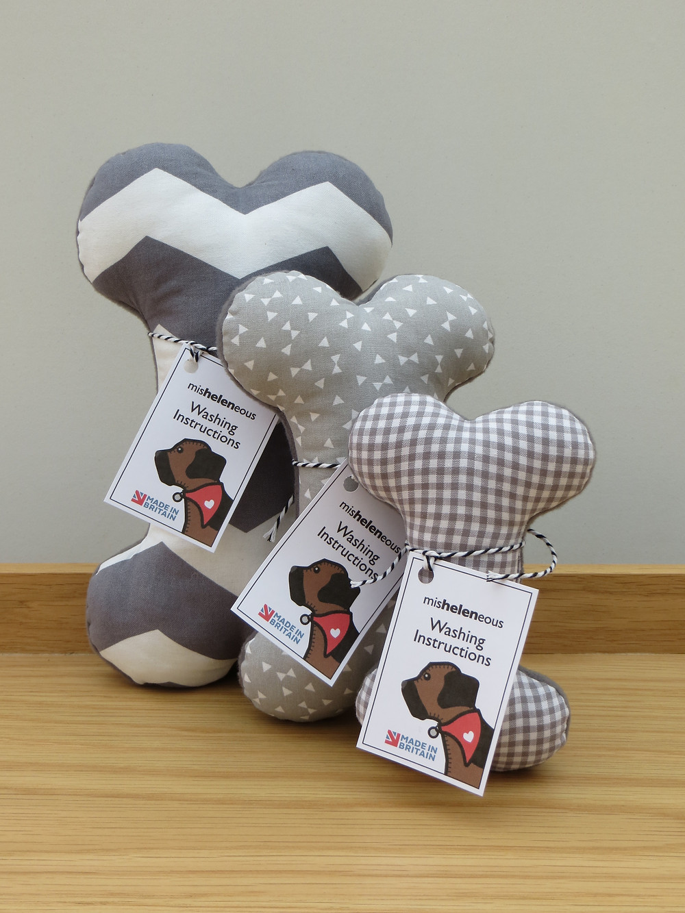 a set of three dog toy bones in 3 different sizes and a variety of grey print fabrics