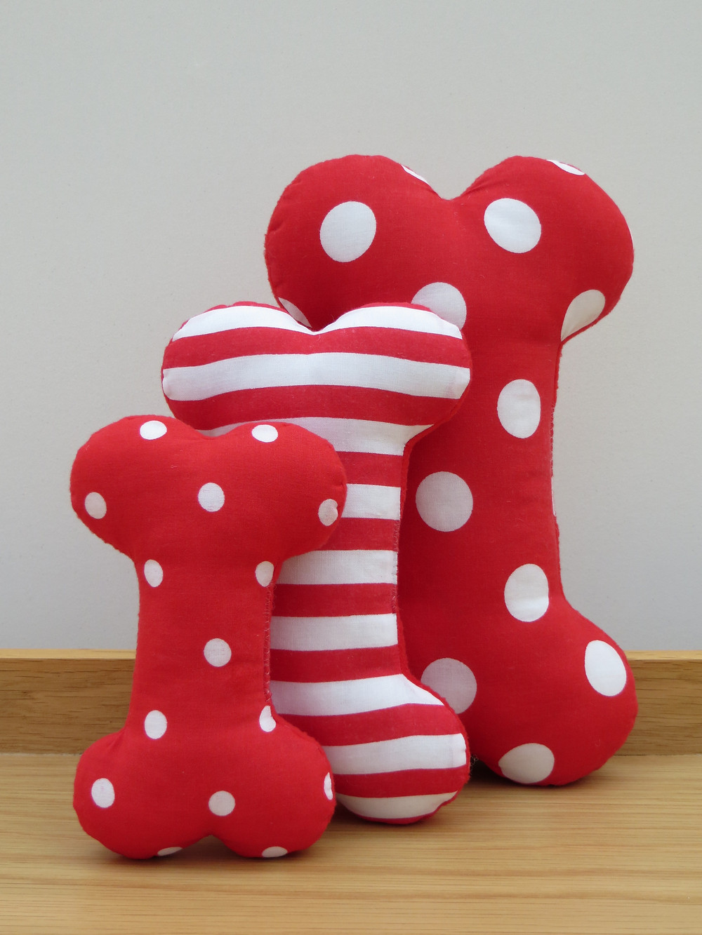 a set of three dog toy bones in red and white fabric with spots and stripes designs