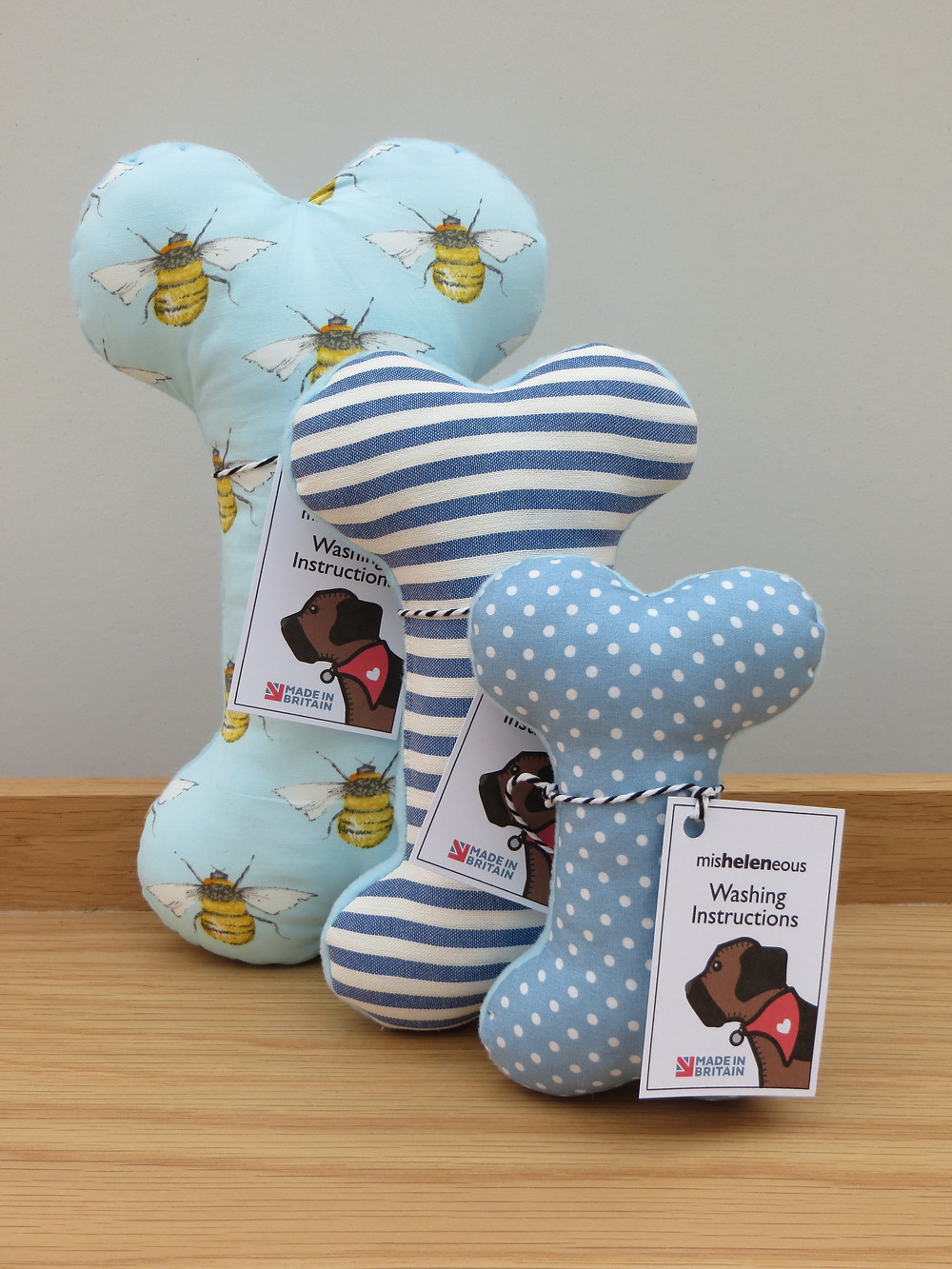 Three fabric dog toy bones in 3 different sizes and prints including bee motif stripes and spots