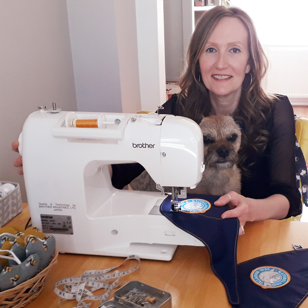 Woman and border terrier sat at a sewing machine