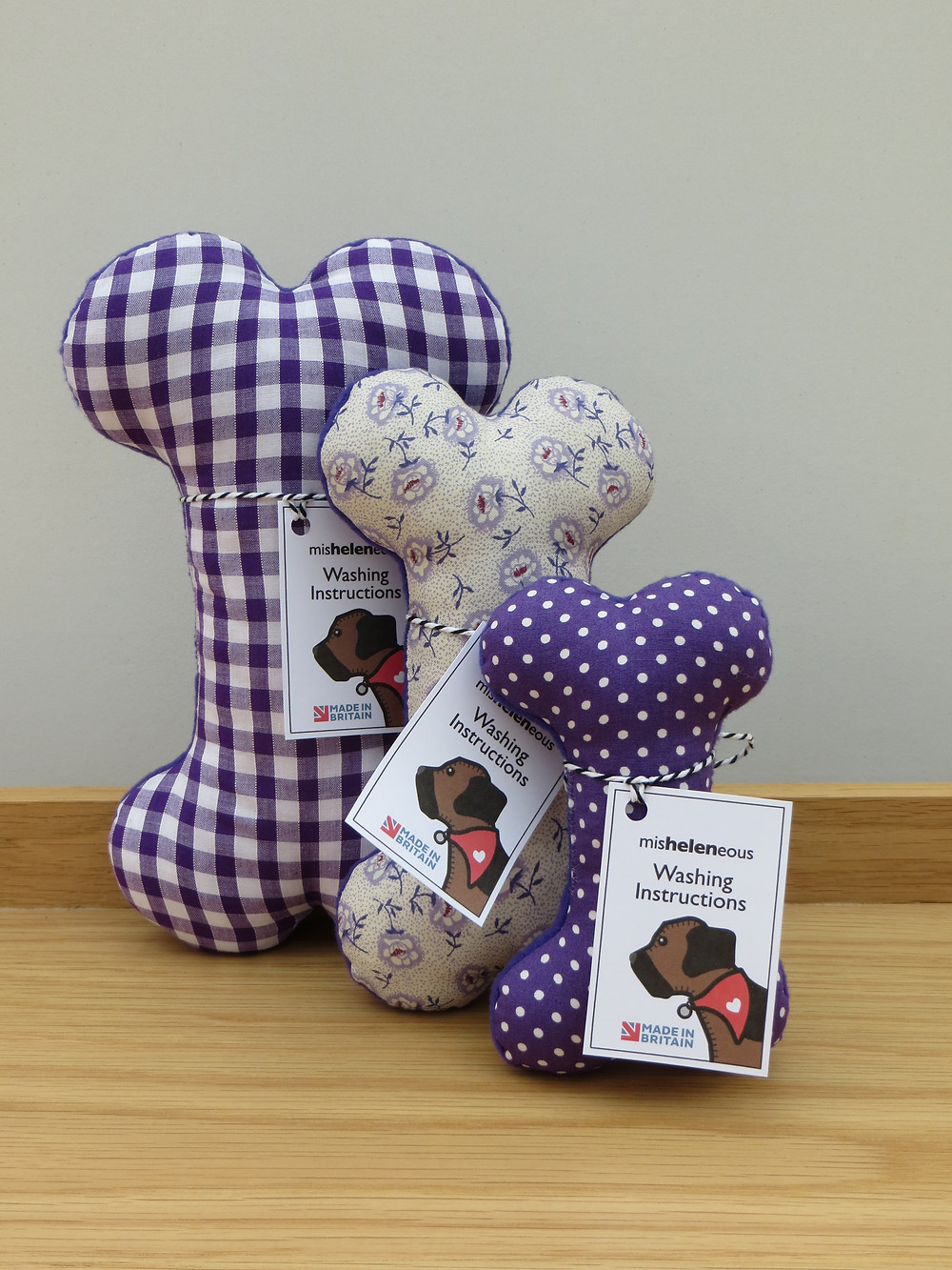 a set of three dog toy bones in purple fabrics in small medium and large and in fabric prints of gingham floral and spotty