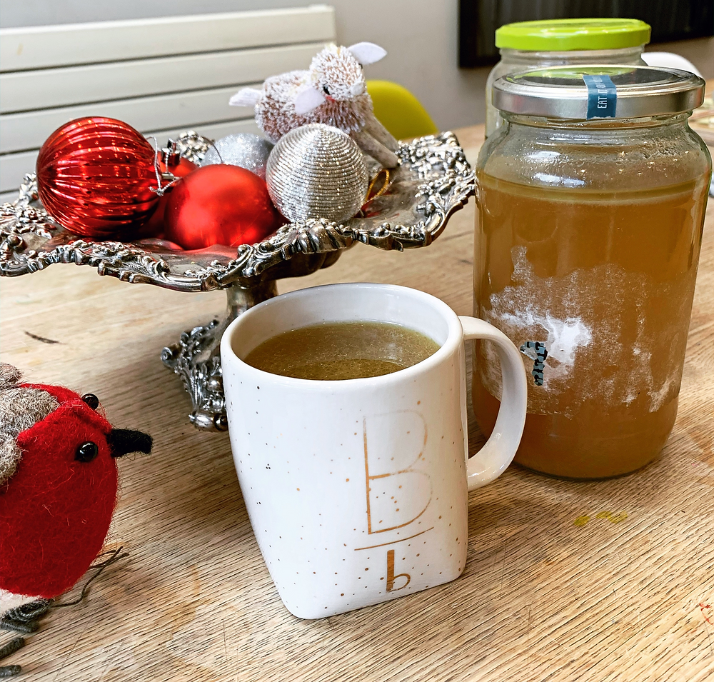 Turkey bone broth in a mug and jar.