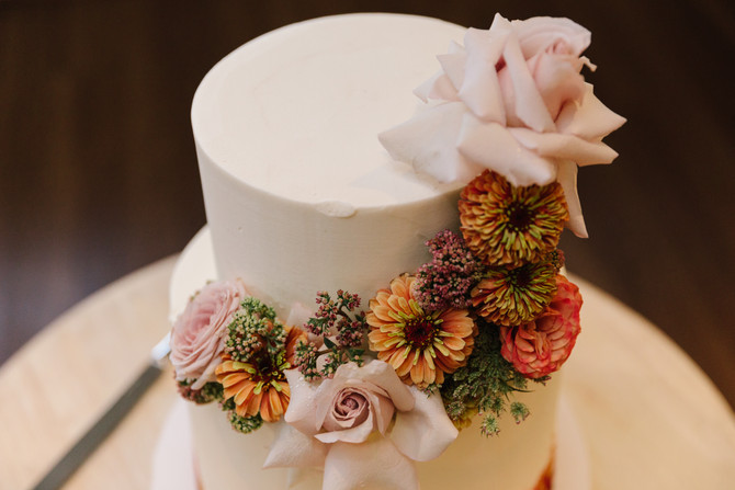 Wedding cake with flowers arranged trailing from top to bottom. Flowers include large reflexed soft pink roses, orange and yellow zinnias and pink sedum. Made by Hobart wedding florist Little Wilderness.