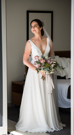Bride holding her wedding bouquet in hotel room. Floral bouquet features soft pink roses, pink king protea and gum leaf, with a soft pink lace ribbon. Made by Hobart wedding florist Little Wilderness.