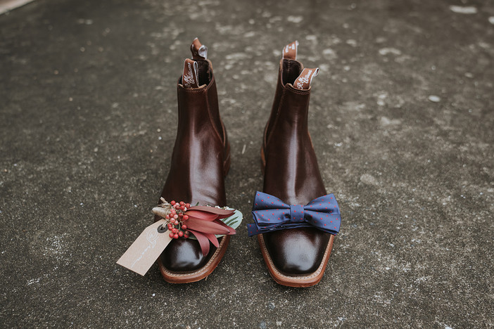 Boutonniere/Buttonhole sitting on one RM Williams boots with blue bow tie on the other boot.