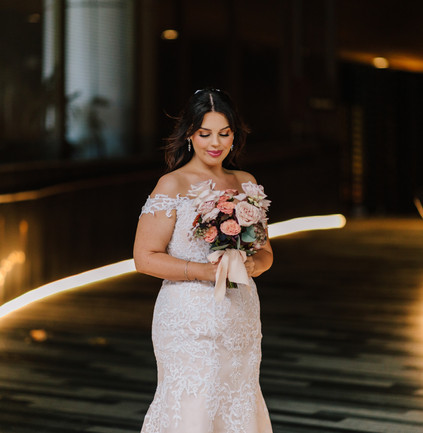 Bride holding her wedding bouquet in the city. Floral bouquet features soft pink roses, orange and yellow zinnias and gum leaf, with a soft pink lace ribbon. Made by Hobart wedding florist Little Wilderness.