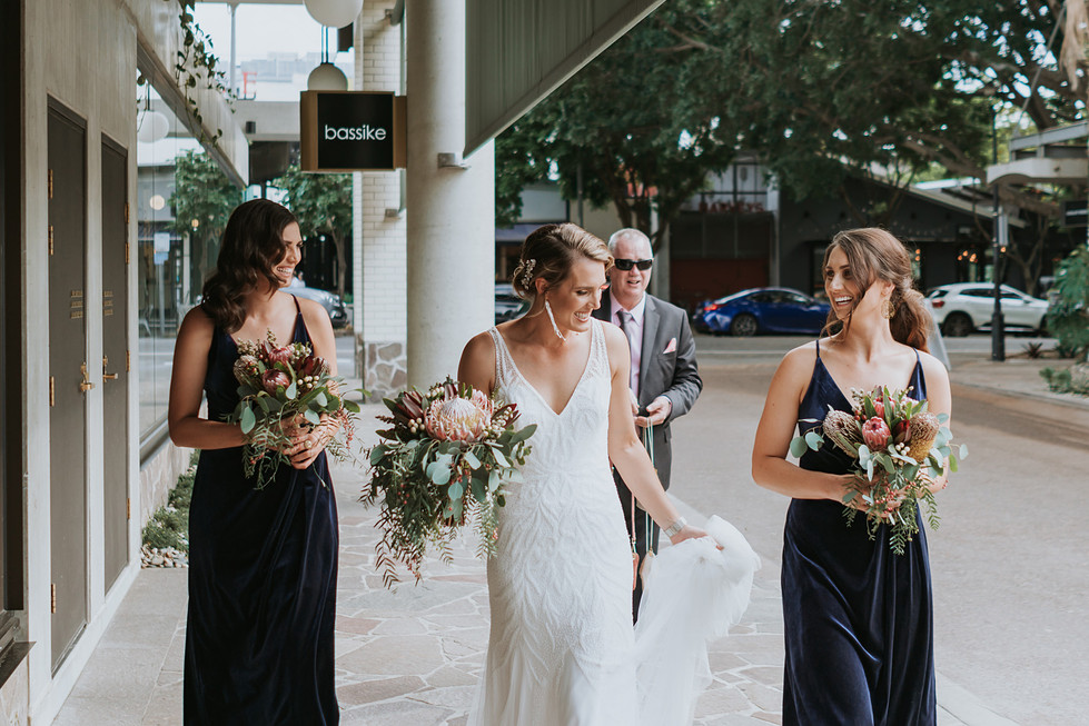 Bride and bridal party walking through the city holding native floral bouquets. Made by Hobart wedding florist Little Wilderness.