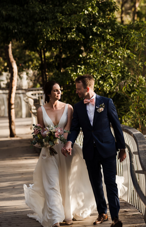 Bride and groom walking along Noosa boardwalk. Bride holding wedding bouquet featuring soft pink roses, pink king protea, gum and a soft pink lace ribbon. Made by Hobart wedding florist Little Wilderness.