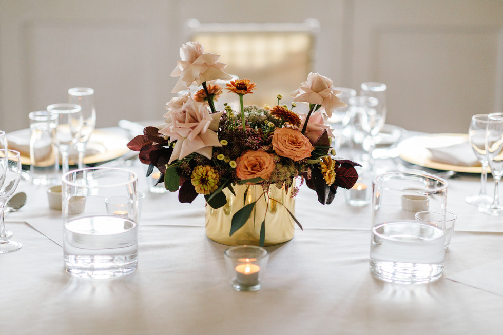 Stylish and colourful floral arrangement, made using sustainable floristry practices. Soft pink roses, yellow and orange zinnias, pink sedum and olive foliage in a gold vase. Made by Hobart wedding florist Little Wilderness.