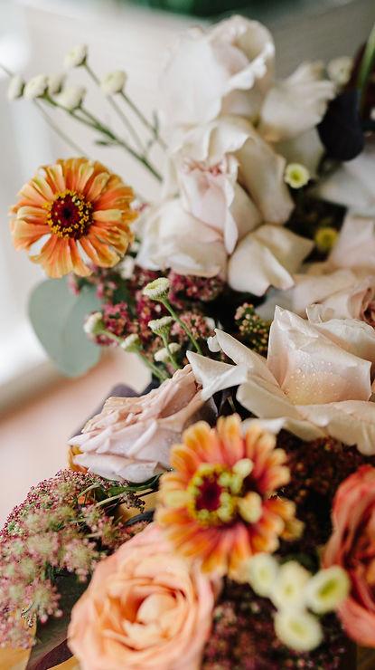 Close up image of flower arrangement featuring orange zinnias, soft pink reflexed roses, daisy flowers, chocolate lace and pink sedum. Made by Hobart wedding florist Little Wilderness.