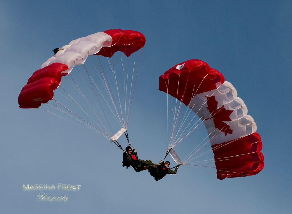 A group of three Canadian Military Skyhawks in formation with their Canadian Flag parachutes