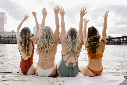 Four women on Willamette River in Portland Oregon in swimsuits backs to the camera with hands in the air. Babylights, Rooted Babylights, Foilayage and Handpainted Highlights for hair photoshoot all colored, cut and styled by Tessa Matsis Smith.