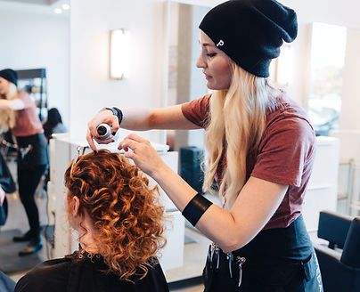Tessa Matsis Smith is curling a her clients red hair at the salon, wearing a Portland Gear beanie