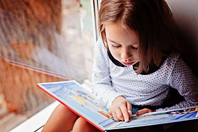 toddler girl with book near the window.j