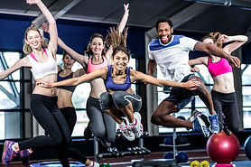 Fit group smiling and jumping in gym.jpg