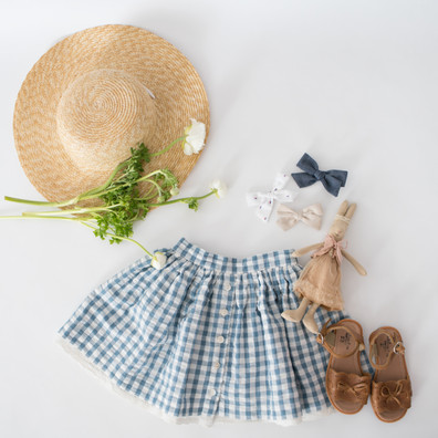 studio, commercial, flat lay, natural light, shoes, hat, skirt, doll