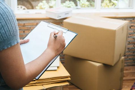 Happy woman checking stuff in cardboard