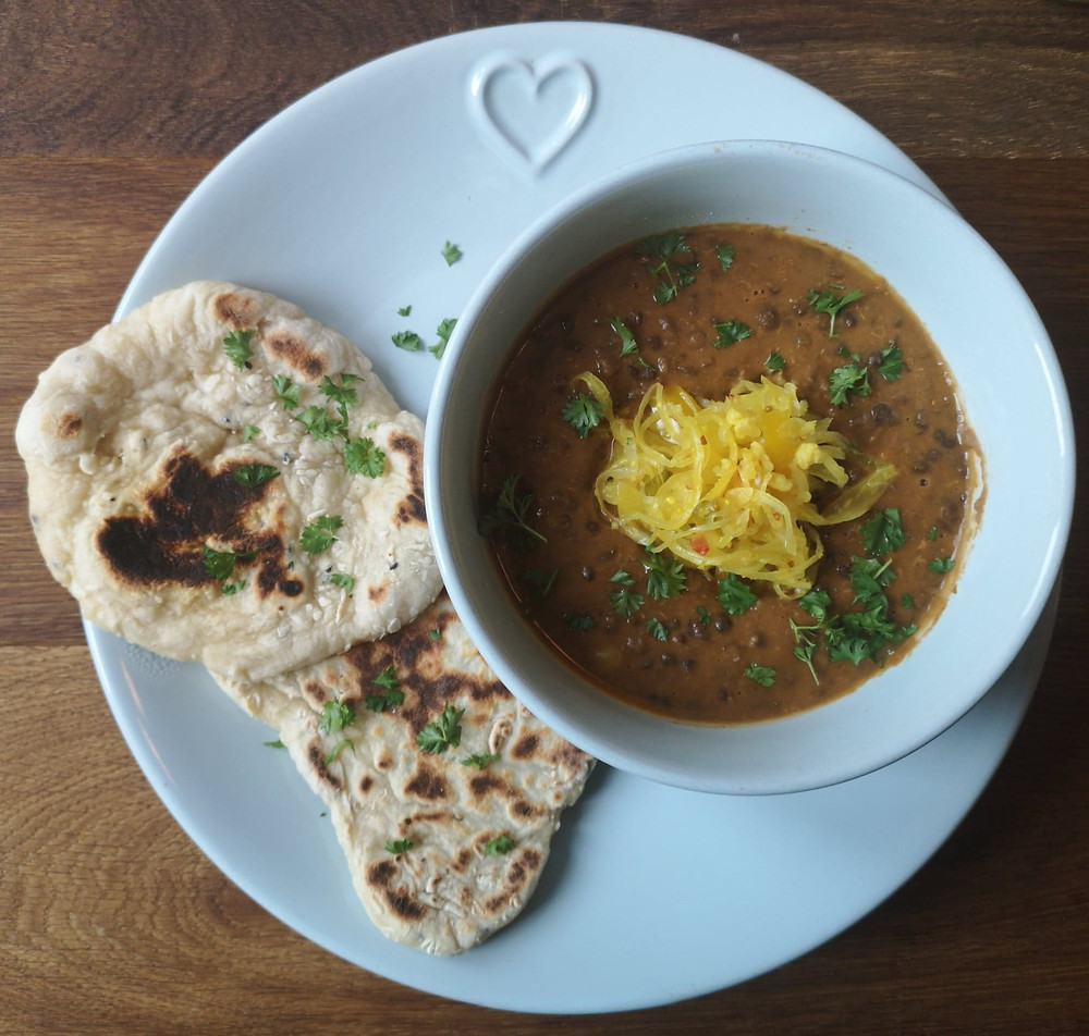 Close up black dal in blue bowl with not your nanas piccalilli sauerkraut and homemade flatbreads