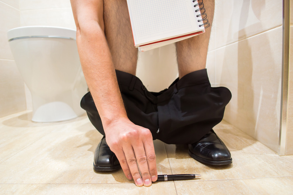 Man sat on the toilet with his trousers down writing in a diary about his stool or poop movements