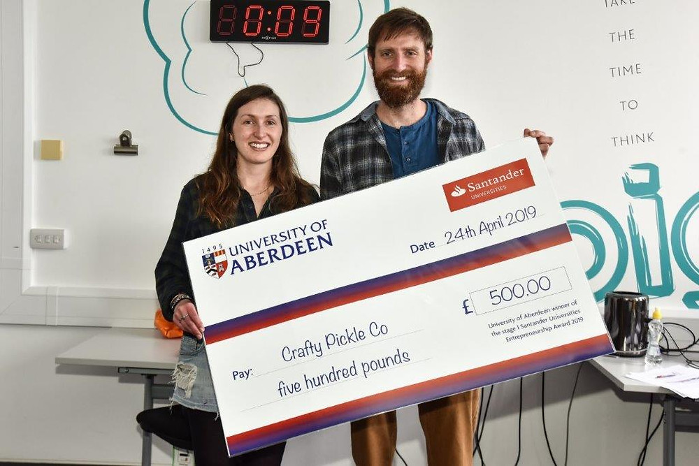 The Crafty Pickle Co. founders Arthur and Madi accepting cheque from the University of Aberdeen
