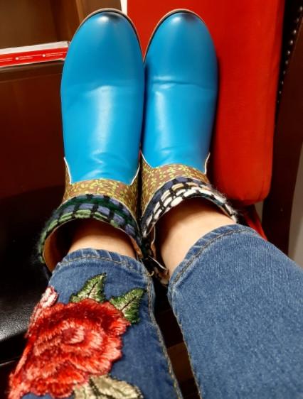 נעלים בצבע תכלת על רגליים עם ג'ינס ושושנה