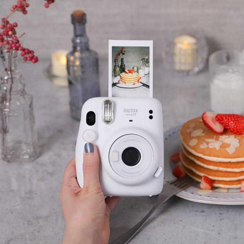 מצלמת אינסטקס מיני 11 לבנה עם תמונה על רקע פנקייק