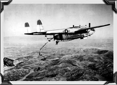 Troops dropping over the Korean hills from C-119