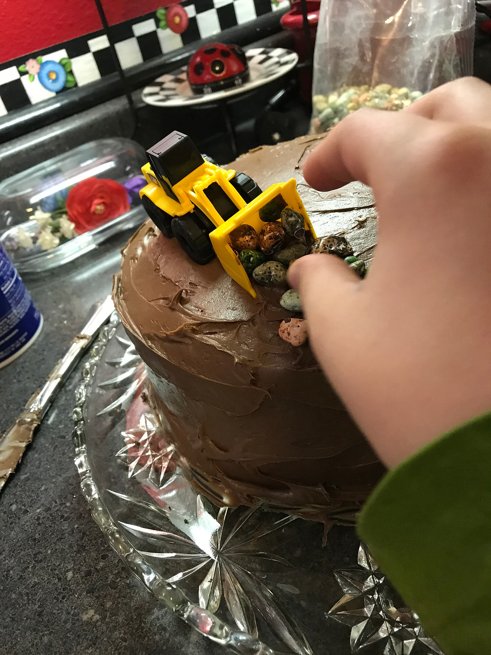 Weston's hand putting a vehicle and rocks on the cake top / Make a Construction Site Cake! / www.HoneycombOasis.com