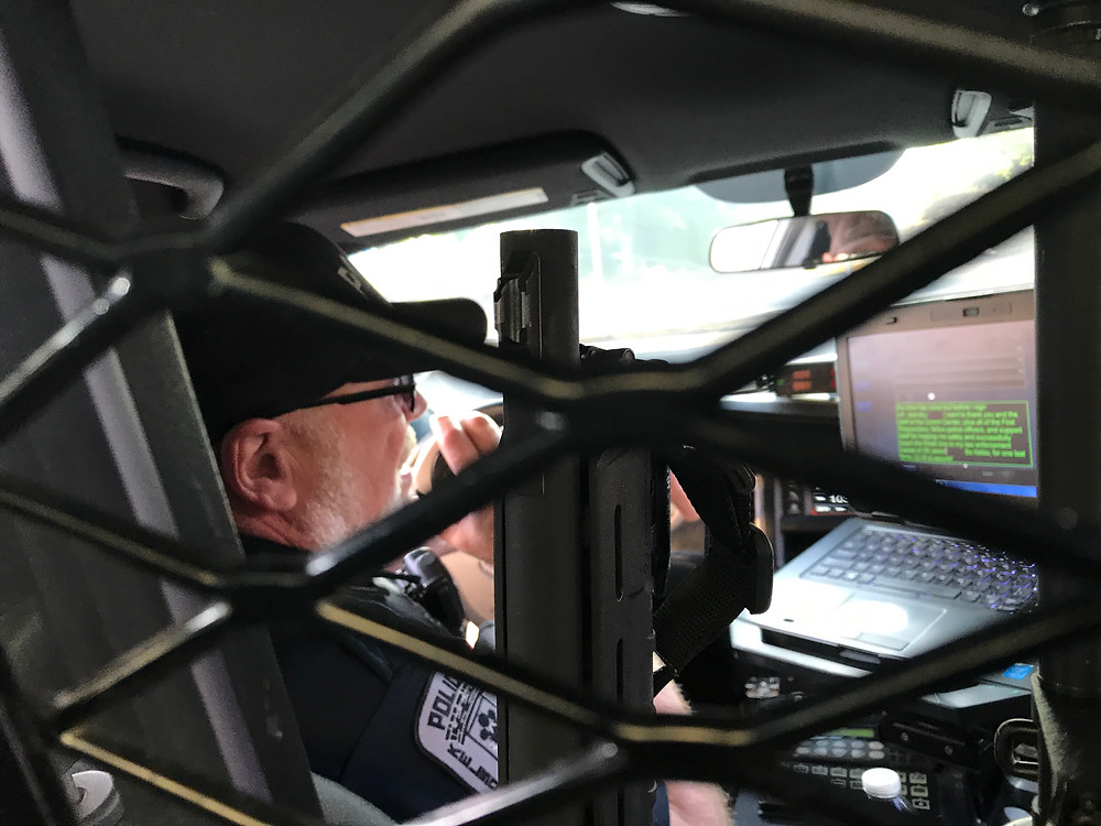 Dave signing off, through grid of the back seat of cop car / Cop's Last Shift & Final Sign-off / HoneycombOasis.com