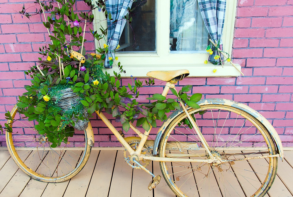 Bicycle planter against pink brick building / Commune With Me Guide / www.HoneycombOasis.com