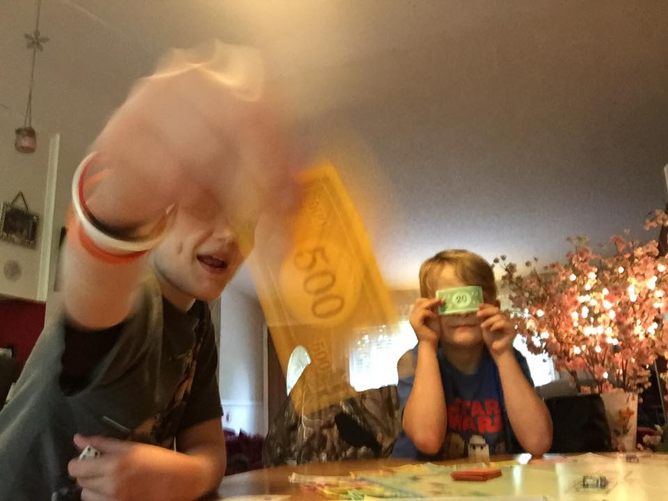 Chase swishing money; Weston with a 20 over his eyes / My Most Rousing Game of Monopoly. EVER! / www.HoneycombOasis.com
