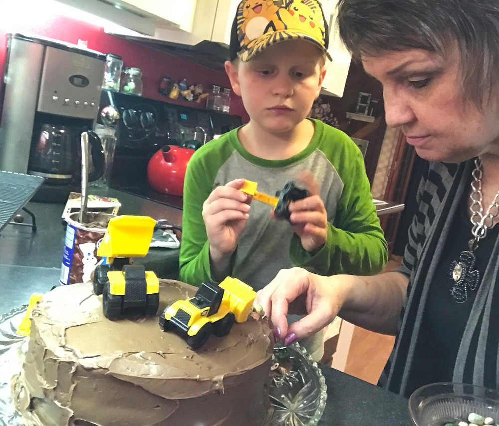 Weston and Gramma putting trucks on the cake / Make a Construction Site Cake! / www.HoneycombOasis.com