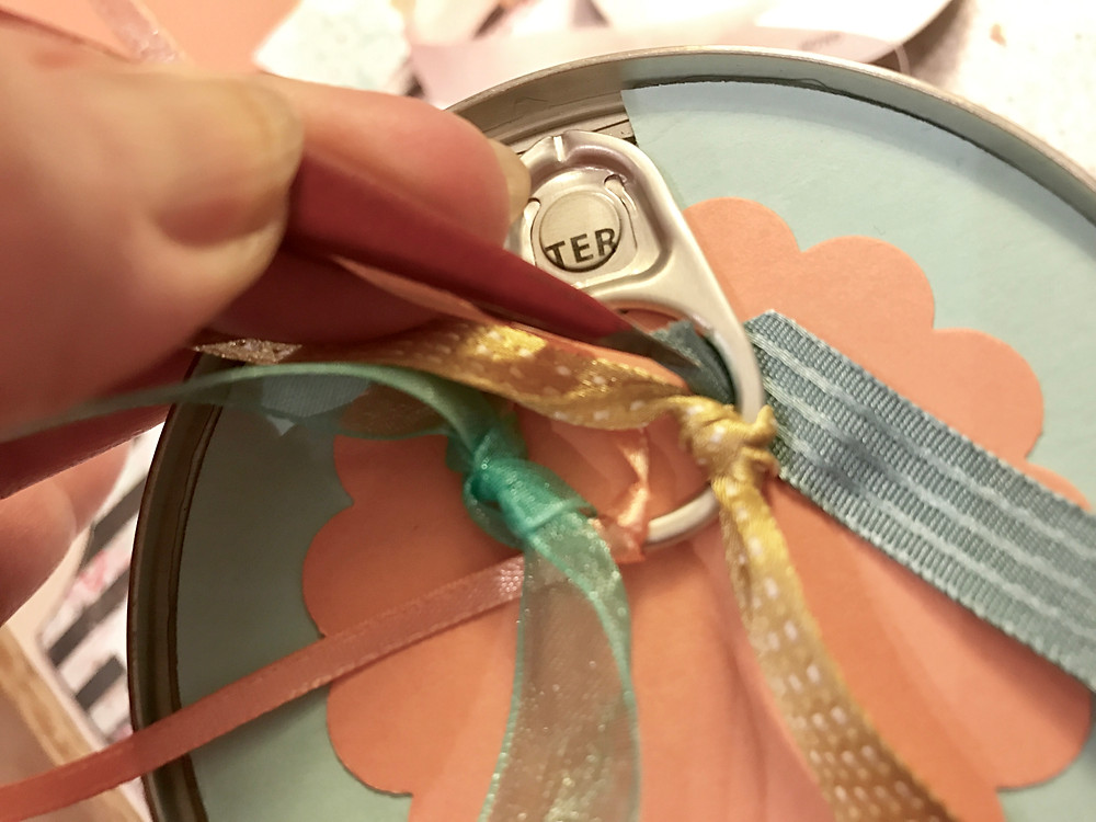 First 3 ribbons tied onto the top of a can pull-ring; pulling in a fourth / Gift-in-a-Can: Decorating It  (Part 3) / www.HoneycombOasis.com
