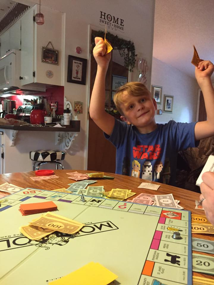 Weston victoriously holding up money / My Most Rousing Game of Monopoly. EVER! / www.HoneycombOasis.com
