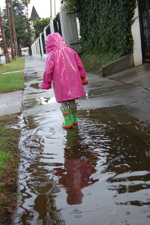 little girl in pink raincoat and boots, in puddle / How to Enjoy Rainy Days Even If You Hate Rain / www.HoneycombOasis.com